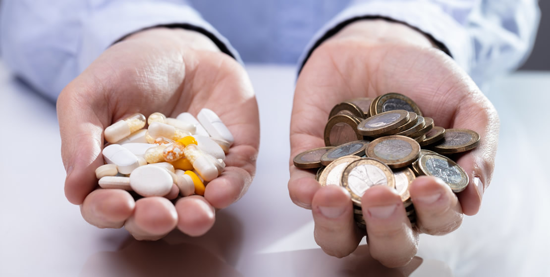 Picture of Person's Hand holding pills on one and coins on the other